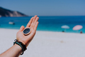 Stretched hand palm with black metal compass against sandy beach and blue sea. Follow your way, goal - PhotoDune Item for Sale