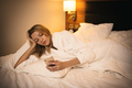 Young Woman Using Smartphone. Lying On Bed In Bedroom. - PhotoDune Item for Sale