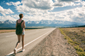 Young Woman Backpacker Walking On Road. Mountains At Background. - PhotoDune Item for Sale