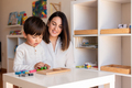 Kid playing with a tetris wood puzzle and mother or teacher help. Homeshooling. - PhotoDune Item for Sale