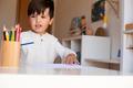 Preschooler kid drawing with coloured pencils. Homeschooling. Learning community. Montessori school. - PhotoDune Item for Sale