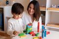 Preschooler Kid playing with wood blocks and teacher educador help. Homeshooling. - PhotoDune Item for Sale