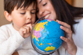 Preschooler Kid learing geography with a globe map and teacher educador help. Homeshooling. - PhotoDune Item for Sale