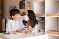 Kid playing tetris wood puzzle with teacher educador help using face mask for coronavirus pandemic. - PhotoDune Item for Sale