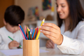 Preschooler kid drawing with coloured pencils with mother or teacher educator. Focus on the pencils. - PhotoDune Item for Sale