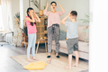 mother in blouse and jeans plays funny game with little son and teenage daughter - PhotoDune Item for Sale