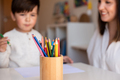 Kid drawing with coloured pencils with mother or teacher educator. Focus on the pencils. - PhotoDune Item for Sale