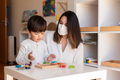 Kid playing tetris wood puzzle with teacher educador help using face mask for coronavirus pandemic - PhotoDune Item for Sale