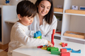 Kid playing with wood blocks and teacher educador help. - PhotoDune Item for Sale