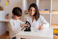 Kid exploring science with a microscope and mother or teacher help. - PhotoDune Item for Sale