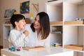 Kid playing with a tetris wood puzzle and mother or teacher help. - PhotoDune Item for Sale