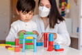 Kid playing with wood blocks and teacher educador help using face mask for coronavirus pandemic. - PhotoDune Item for Sale