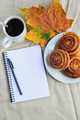 cinnamon rolls with topping on plate, cup of coffee, open notepad and pen, autumn leaf on table - PhotoDune Item for Sale