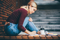 Pretty girl student writes in paper notebook sitting on stone bench with thermo cup in city street. - PhotoDune Item for Sale