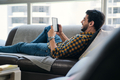 Man Reading Ebook With Ereader Lying On Couch - PhotoDune Item for Sale