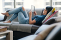 Young Woman Reading Ebook With Ereader On Couch - PhotoDune Item for Sale
