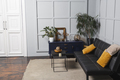Bright apartment interior with black leather sofa, decorated wall lamp and table. - PhotoDune Item for Sale