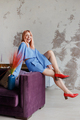 Happy alone woman at home on sofa in casual clothes and red shoes - PhotoDune Item for Sale