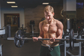 Muscular man working out in gym doing exercises with barbell at biceps, beginner male - PhotoDune Item for Sale