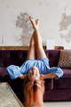 Beautiful woman relaxing on a sofa with head upside down at home - PhotoDune Item for Sale