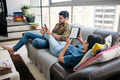 Young Couple Reading Ebook With Ereader On Couch - PhotoDune Item for Sale