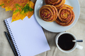 cinnamon buns with topping on plate, cup of coffee, open notepad and pen, autumn leaf on table - PhotoDune Item for Sale