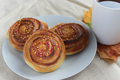cinnamon rolls or buns with sugar sprinkle topping on white plate and cup of black tea on table - PhotoDune Item for Sale