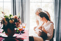 Young woman breastfeeds baby and talks to grey haired mother. - PhotoDune Item for Sale