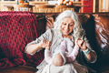 Aged lady with long loose grey hair plays with little granddaughter - PhotoDune Item for Sale