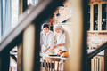 Young woman and mother in white aprons prepare tasty dinner. - PhotoDune Item for Sale