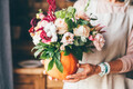 Pumpkin with beautiful bouquet of flowers in woman hands. - PhotoDune Item for Sale