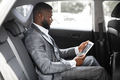 Concentrated black guy manager using digital tablet in car - PhotoDune Item for Sale