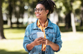 African Student Girl Using Cellphone Walking On Weekend In Park - PhotoDune Item for Sale