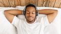 African Man Listening Music Wearing Headphones Lying In Bed Indoors - PhotoDune Item for Sale
