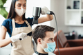 Hairdresser in protective mask making hairstyle for male client, dying his hair - PhotoDune Item for Sale