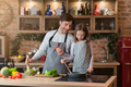 Young man and his little daughter cooking together in kitchen - PhotoDune Item for Sale