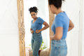 Discontented African Girl Touching Fat Belly Standing Near Mirror Indoor - PhotoDune Item for Sale