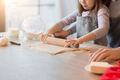 Father and daughter rolling dough together in kitchen to make cookies, cropped - PhotoDune Item for Sale