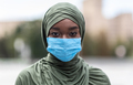 Portrait of black muslim woman wearing blue medical protective face mask outdoors - PhotoDune Item for Sale