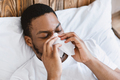 Sick African Guy Blowing Nose In Tissue Lying In Bed - PhotoDune Item for Sale