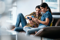 Young Man Helping Girlfriend With Phone App at Home - PhotoDune Item for Sale