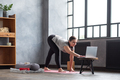 Woman practicing yoga, stretching legs in parshvatanasana during online lesson - PhotoDune Item for Sale