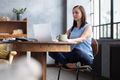Relaxing businesswoman sitting near table in lotus pose - PhotoDune Item for Sale