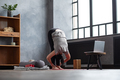 Woman working out indoors standing in Uttanasana during online lesson. - PhotoDune Item for Sale