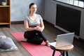 Smiling woman sitting on yoga mat using laptop in bright room - PhotoDune Item for Sale