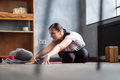 Woman working out indoors, doing variation of twisted forward bend yoga exercise - PhotoDune Item for Sale