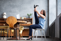 Woman practicing heron pose sitting at home relaxing during hard working day. - PhotoDune Item for Sale