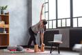 Young woman practicing yoga, doing Revolved Triangle Pose, Parivrrta Trikonasana - PhotoDune Item for Sale