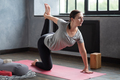 Young woman working out at home doing yoga, pilates balancing exercise - PhotoDune Item for Sale