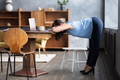 Woman working out doing yoga exercise standing in Uttanasana using on table. - PhotoDune Item for Sale